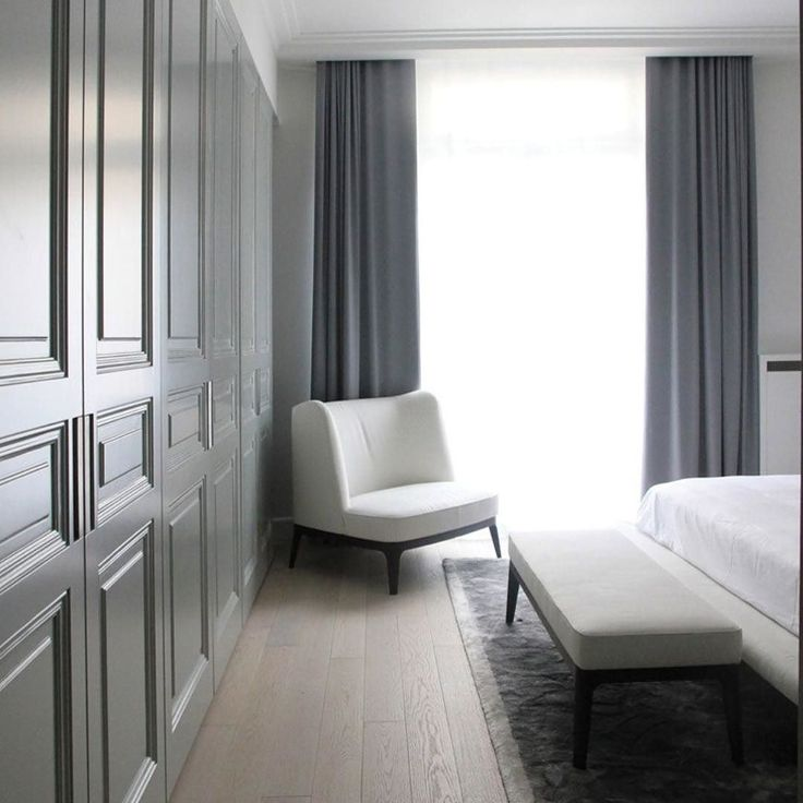 Simple clean grayscale bedroom. Paneled grey closets
