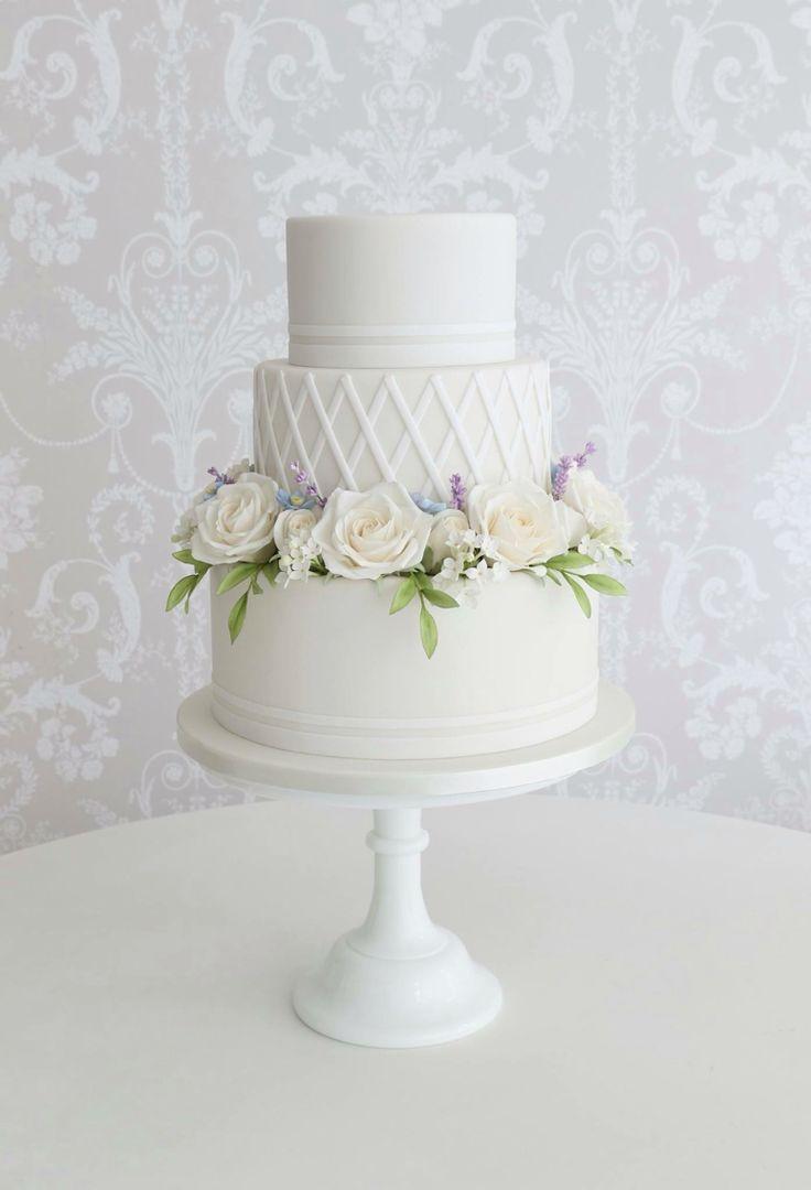 Sugar Roses, lilacs, blue Narcissus and foliage around trellis wedding cake design by Zoe Clark