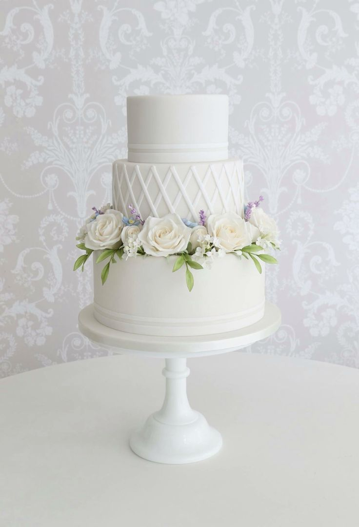 Sugar Roses, lilacs, blue Narcissus and foliage around trellis wedding cake design by Zoe Clark
