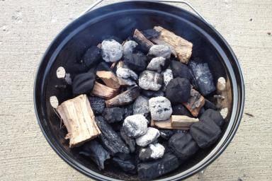 In the bottom of the Smokey Joe, unlit charcoal (lump and briquettes) and hickory wood. - David Reber/Flickr
