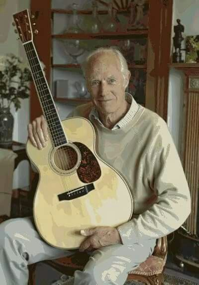 """George Martin with a """"M3M George Martin Studio Edition"""" guitar from a Martin Guitar Company. Each """"M3M Martin Studio Edition"""" guitar bears an interior label personally signed by Sir George Martin and Martin Chairman C.F. Martin IV. This Guitar has a small """"5"""" inlay at the fifth fret to commemorate George Martin's role as the fifth Beatle and GM's signature is inlaid between the 19th and 20th frets."""