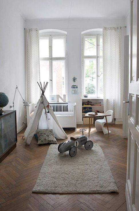 small playroom with herringbone floors and neutral furnishings.