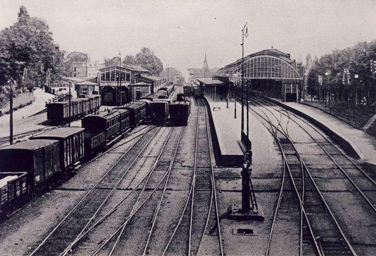 Arnhem: Het Arnhemse treinstation rond 1900, gefotografeerd vanaf het viaduct bij de Brugstraat. Rechts de in 1890 gebouwde overkapping van de twee perrons. In die overkapping bleef volgens de verhalen altijd veel rook van de stoomlocomotieven hangen. Links de goederen/douaneloods.