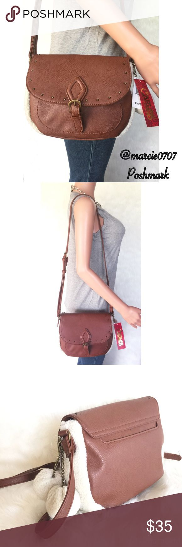 Carlos Santana handbag Carlos Santana Quincy saddle crossbody handbag. Brown color Cognac with cream fluffy material around the outside and cream fluff balls. Has bronze/gold color metal buckle on the front and one on the strap. One open pocket on the back. One zipper pocket on the inside and two pockets on the other side. Carlos Santana Bags Crossbody Bags