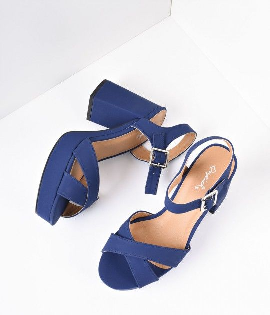Pin-up panache at its finest! A pair of wondrous block heels, these sandals boast a criss cross vamp with a chic peep toe. The tidily trim silver-buckled ankle strap is adjustable and gored, offset by a canvas covered 1.5 inch platform and 4 inch heel. <b