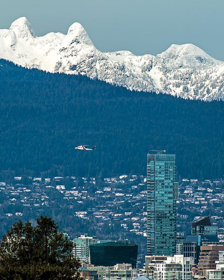 """Sky Pilot  Helijet's BC Air Ambulance flys by the Shangri-La Hotel Vancity's tallest building. In the distance the British Properties on the north shore mountains and """"The Lions"""" covered with snow. The Lions Gate Bridge and the BC Lions CFL Football Team are named in honour of these two peaks. Captured this afternoon from Queen Elizabeth Park in Vancouver BC  January 19 2016"""