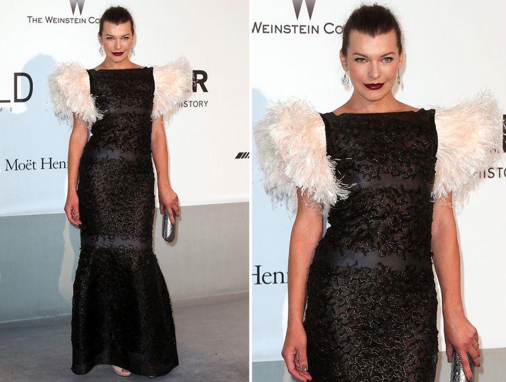 MILLA JOVOVICH Artis film Resident Evil tampil menawan dengan gaun hitam rancangan Chanel yang dihiasi bulu-bulu di bagian pundak.