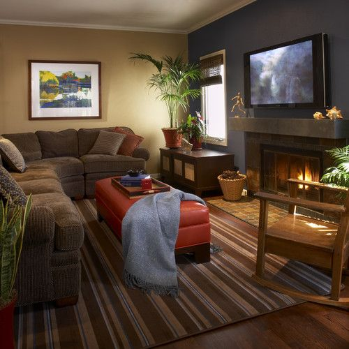 Cozy family room. Gray and brown walls, small organizing shelf under the window with plants on top, brown sectional couch with ottoman as a coffee table and tv over the fireplace.