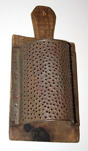 Up for bids we offer this old, rustic,  grater in excellent condition. Primitively made long ago from an old wooden breadboard and a hand-punched piece of tin, this grater is just as we found it. The wood old patina The tin ist surface rust which adds to its folksy appearance. Overall, this grater measures 12 3/4 in h, 6 1/4 in L & 3 3/4 in w.  Hand carved handle with a hole which was originally used for hanging , It's a unique, untouched offer up for bids . Sold for $86.00 plus shipping