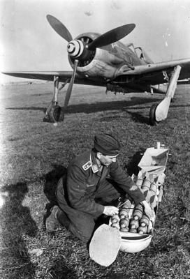 A German aircraft technician prepares a cluster bomb for the fighter-bomber Focke-Wulf Fw 190F. - The Focke-Wulf Fw 190 was a German single-...