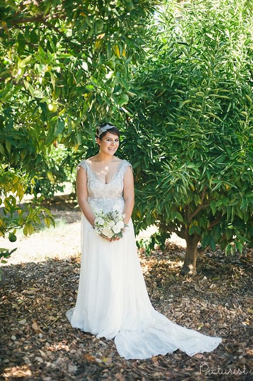 Beautiful wedding dress with cute short hair do and hair piece. Lovely white bouquet. From Carla & Werner's wedding at Maison Estate in Franschhoek.