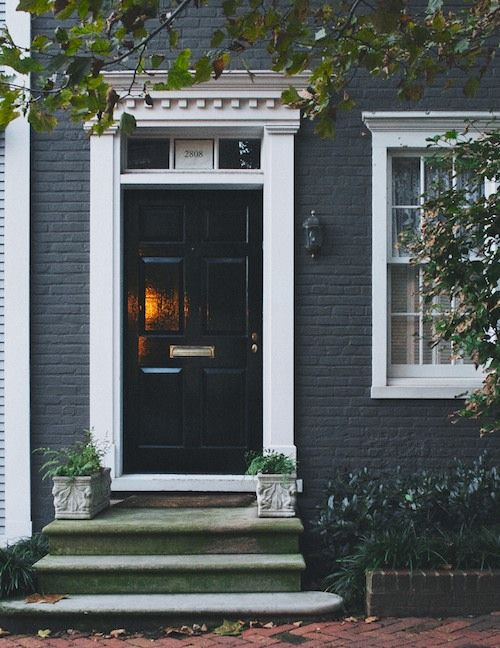 wonderful high gloss black door with a pediment, pilasters and white window casing- brick painted a deep charcoal gray