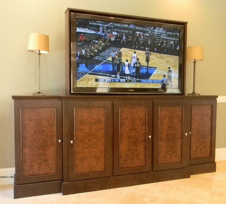 """65 Inch Tv Lift Cabinet. White Ash Burl door panels framed in dark stained maple wood. The cabinet holds a 65 inch television with ease, has component storage areas to the left and right of the television, and has blanket storage behind the television. Bright idea when the TV is not in use, automatically lower it into the JSD TV cabinet to keep it safe from burglars, energetic children, and accidents. Price range $3,000 - $6,000. Dimensions:  112"""" wide x 46"""" tall x 21"""" deep"""