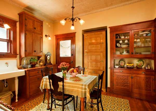 """Unfitted pieces, plain walls, and the center table are in keeping with the period of the house. The """"icebox"""" cabinet in an alcove at center disguises the Miele refrigerator. The cabinet to the right is original. A painted canvas floorcloth protects the floor."""