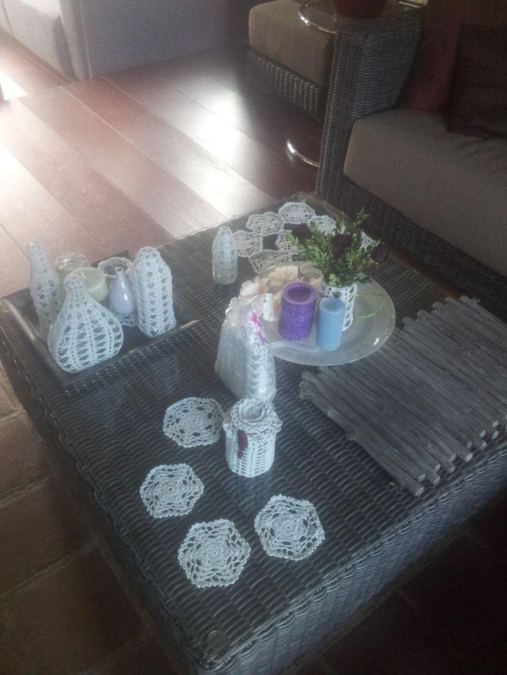 Salontafel met gehaakte onderzetters en flesjes.