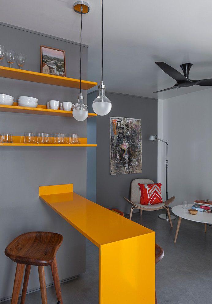 Яркая желтая барная стойка и такие же желтые полочки являются своеобразным украшением и существенно оживляют интерьер квартиры выполненный в серых тонах. .