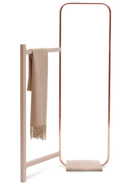 This clothes rack features a copper arc with a hinged timber frame, allowing it to slot into the corner of a room.
