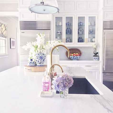 Now this is a dreamy white kitchen. White countertops, lights, and cabinets get a pop of color with flower bouquets.