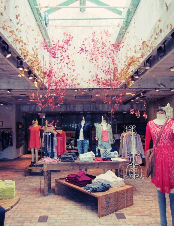 Free People Fall Display inspiration! Bikes wrapped in yarn with leaves woven in the spokes, denim quilts hung from tree branches... fall leaves climbing to the ceiling...ahhh it's beautiful!