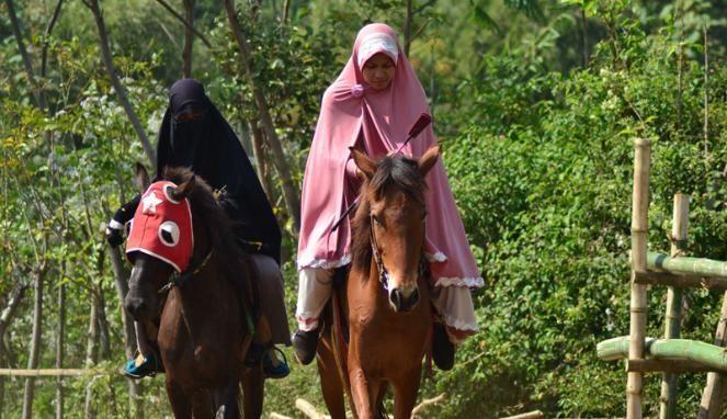 Pesantren Unik, Santri Wanitanya Ajari Memanah dan Berkuda = Santri wanita pondok pesantren An Nashr mengajarkan cara menunggang kuda kepada siswa SD di Desa Giripurno, Kota Batu, Malang.