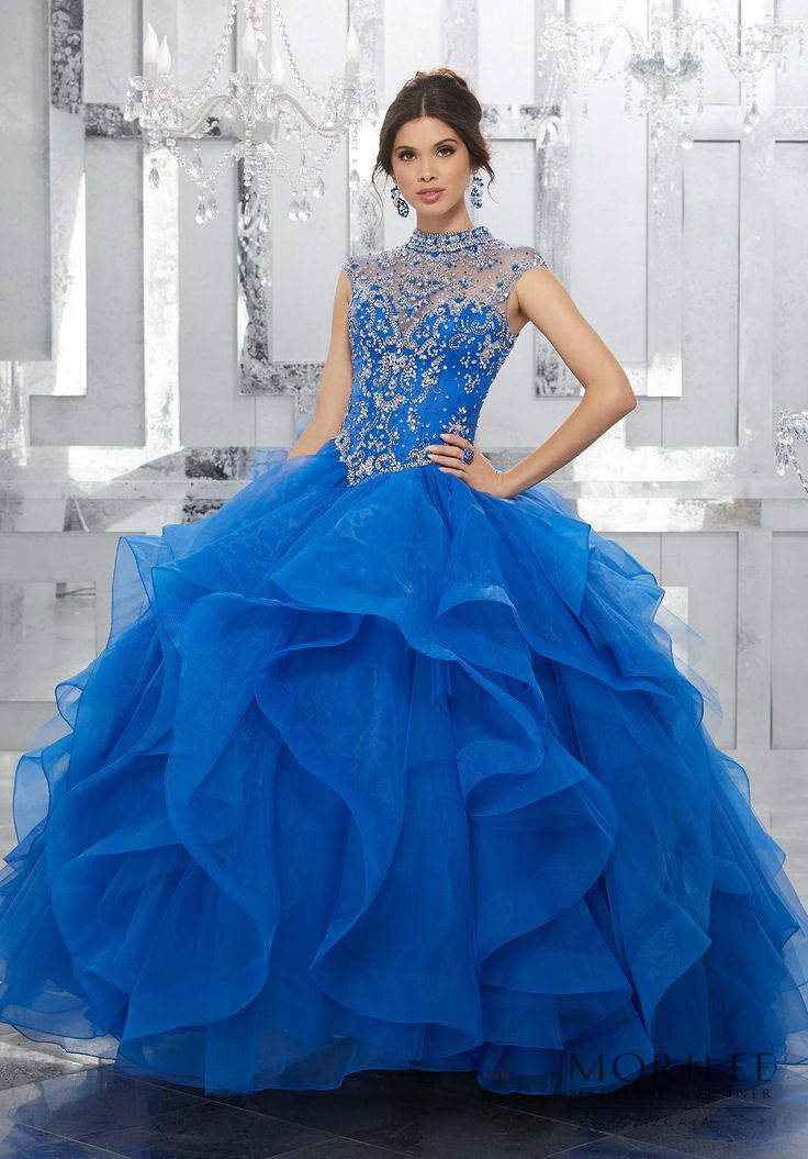 This Beautiful Blue Quinceañera Princess Ball Gown Features a Fully Beaded Bodice Accented with a High Illusion Keyhole Corset Back. A Dreamy Flounced Skirt Completes the Look. Matching Stole Included. Colors Available: Blush, Lilac, Royal, White. Sweet 15 Dress by Vizcaya | Morilee by Madeline Gardner. Style 89155.