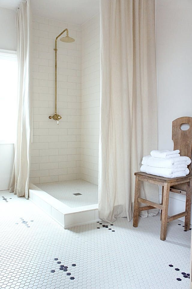 gold shower, off white tiles, penny tiles, wooden chair, stacked towels, cream curtain