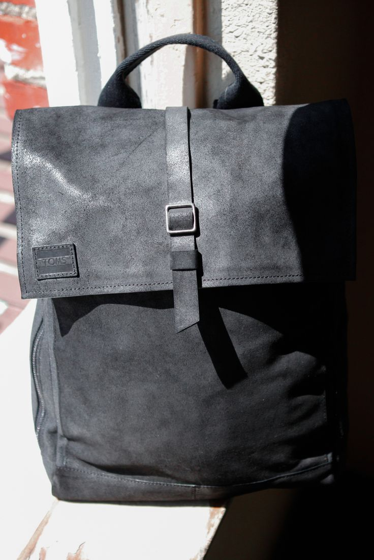 Travel well with this black leather and canvas TOMS Trekker Backpack.