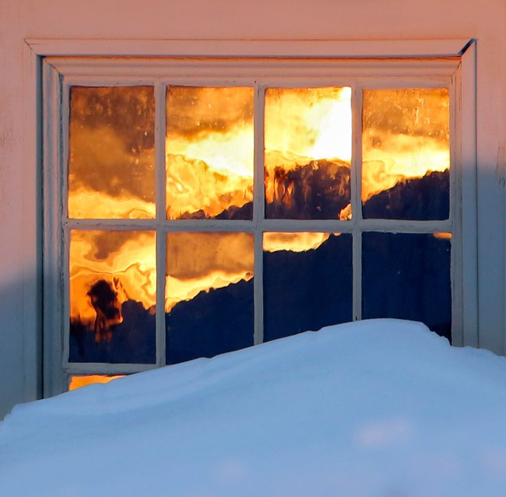 The panes of a snow-mounded door blaze with the color of the setting sun at Laudholm Farm in Wells. Gregory Rec/Staff Photographer