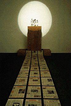 """Antonio Muntadas - """"The Press Conference Room"""" (1991) Architettura mediatica - podio e microfono appaiono come punto focale. L'assenza dell'oratore è sottolineata da uno spot luminoso. I leader appaiono invece in una televisione dall'altra parte della stanza collegati da una fila di giornali. La colonna sonora è realizzata con discorsi di personaggi pubblici che inizialmente sono chiari poi diventano incomprensibili, similmente alla deformazione dei significati che avviene in una arena…"""