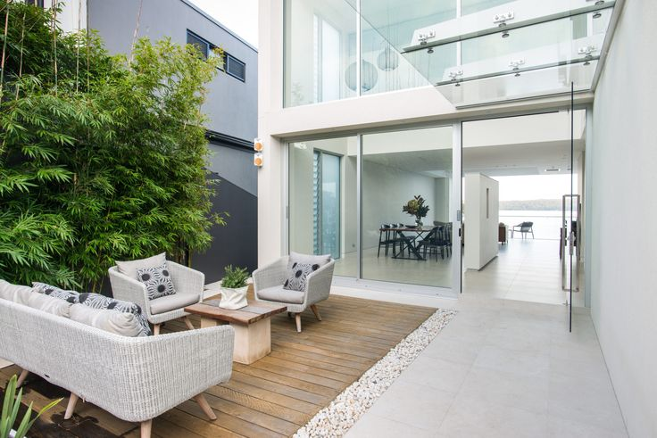 Modern Waterfront home in Sydney | Modern Home | Contemporary house | Sydney architecture | beach house | modern interior | white minimalist design | partition wall | glass sliding doors | designer table | designer chairs | dining room | modern kitchen | white bench top | butlers pantry | view | bay | stair detail | courtyard |