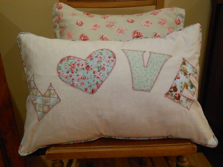 A rectangular cushion with the word -Love - done in mint green.