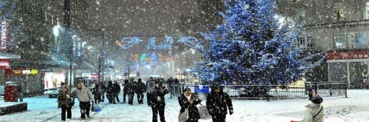 Dunne stuifsneeuw joeg door de straat.  De verlichting van de lantarens en de winkelruiten veranderde het wit in een tijdelijk goudgeel op het moment dat de sneeuw de lichtstraal doorkruiste. H