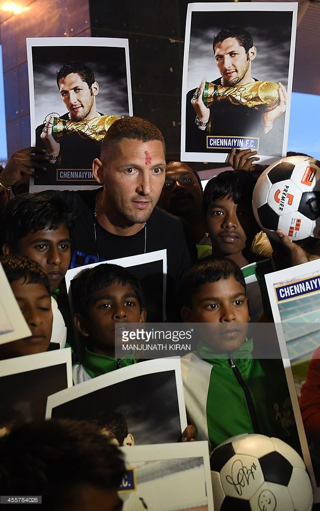 Italian footballer Marco Materazzi (top C) poses with football fans who had gathered at the Kempegowda International Airport to welcome him on his arrival in Bangalore on September 20, 2014. Materazzi, the 41-year-old former Italy defender joined Chennaiyian Football Club in the Indian Super League following in the footsteps of his former national team-mate Alessandro Del Piero. AFP PHOTO/Manjunath KIRAN