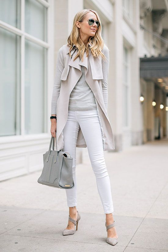 Fashion Blogger 'Fashion Jackson' wearing a light grey trench coat, a light grey light sweater, white skinny jeans, light grey pointy toe heels, mirror aviator sunglasses and a light grey handbag