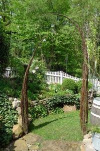 Weidenbündel in Zipfelform als Torbogen im Garten