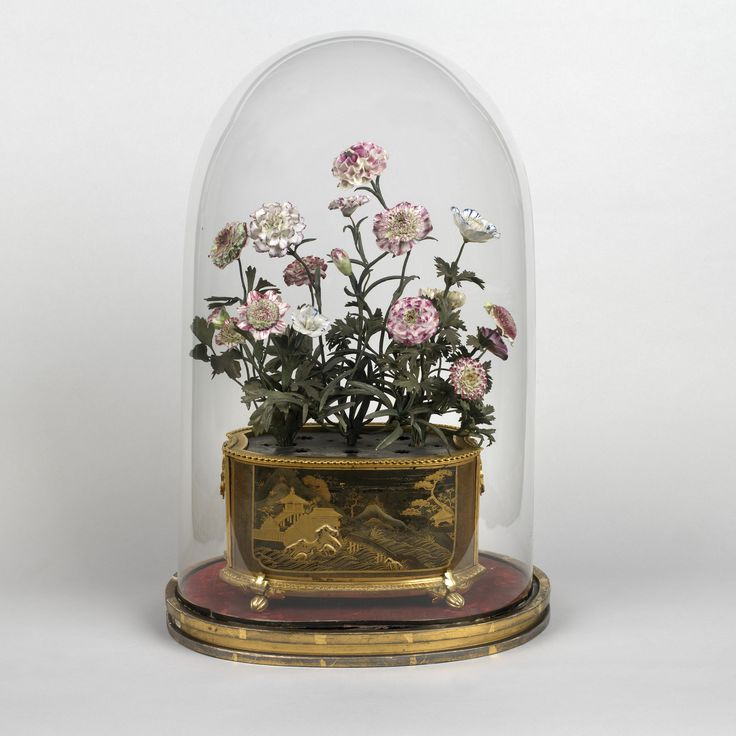 1756. A bouquet of soft-paste Vincennes porcelain flowers with green metal stems and foliage, issuing from an oval Japanese lacquer jardiniere with a cartouche at the front and back depicting a rural scene with vegetation and buildings in the background. The jardiniere, which stands on four feet in the shape of flower buds.