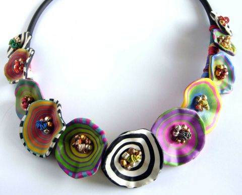 gorgeous polymer clay necklace with many different abstract shaped flowers.