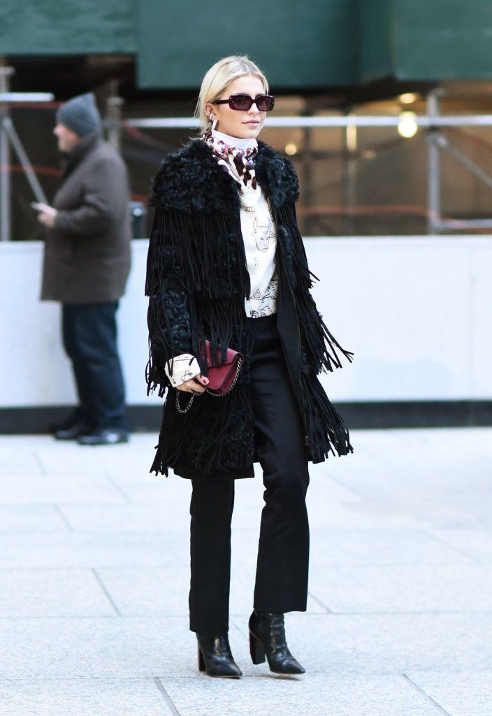 Caroline Daur is seen wearing a black coat, animal print top