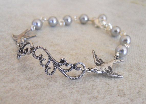 A beautiful filigree flower followed by 2 birds is the center piece of this bracelet. This unique center piece is adorned by gray glass pearls.