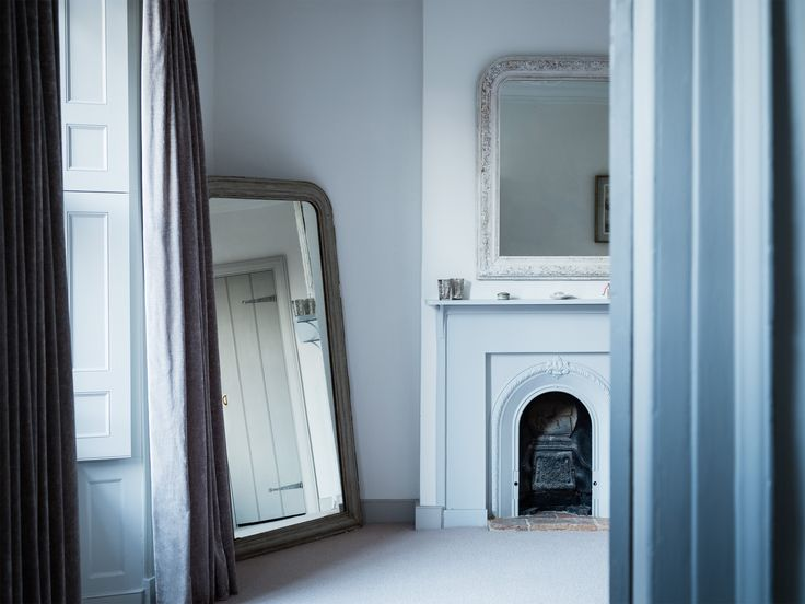 Mirrors in Blue Dorset House by Mark Lewis, Photo by Rory Gardiner  In the master bedroom, antique mirrors sourced from Kempton market flank an original fireplace, updated with Little Greene's Bone China Blue.