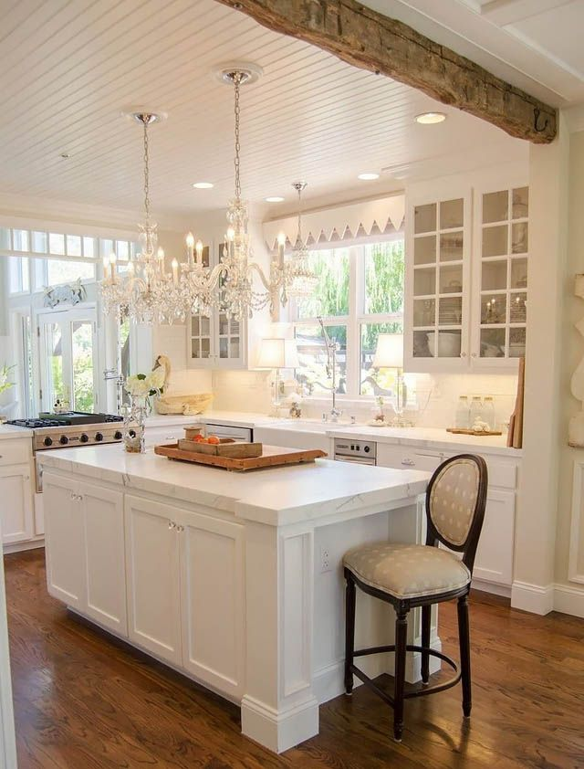 Glamorous Custom Kitchen! Notice very rustic beam with the very shiny crystal chandeliers, so very pretty
