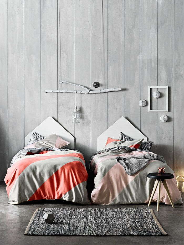 The dominant colour and texture of the panelled walls and wood flooring combined with the simplicity and uniqueness of the individual elements plus a flash of white and coral equals a fantastic Scandi design influenced bedroom for two.