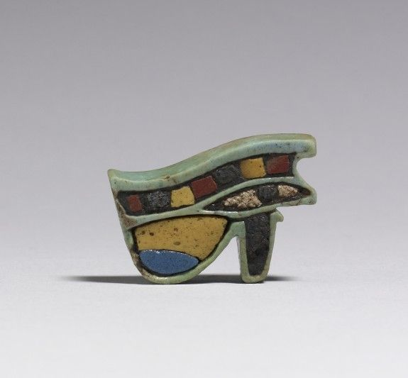 Sacred Eye Udjat or Horus-eye symbolizes legitimate kingship. The amulet combines the human eye with the cheek marking of a falcon and the tear marking of a cheetah. The right eye is connected with the sun, the left eye represents the moon. ca. 945-525 BCE. Egypt. polychrome faience, glass