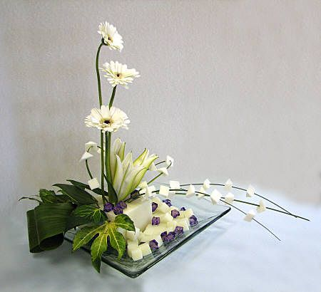 table decor- monstera leaf, calla lilies, orchids, lily of the valley and gold sprayed rocks