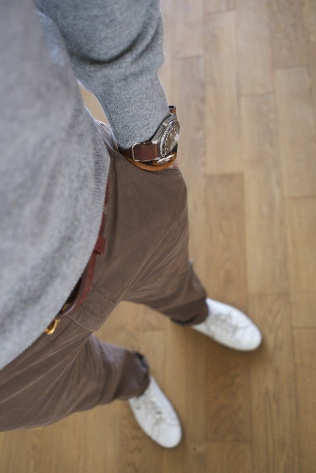grey sweater brown pants white shoes.