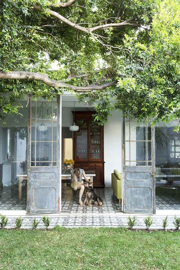 The front exterior of one gorgeous South African home with sliding doors and large tree