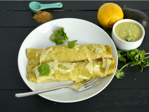 Creamy Avocado Chicken Enchiladas Recipe Main Dishes with avocado, chicken broth, coconut milk, lemon, cumin, chili powder, cayenne pepper, sea salt, black pepper, chicken breasts, red bell pepper, cuban peppers, onions, garlic cloves, black beans, taco seasoning, chicken broth, sauce, whole wheat tortillas, shredded cheddar cheese