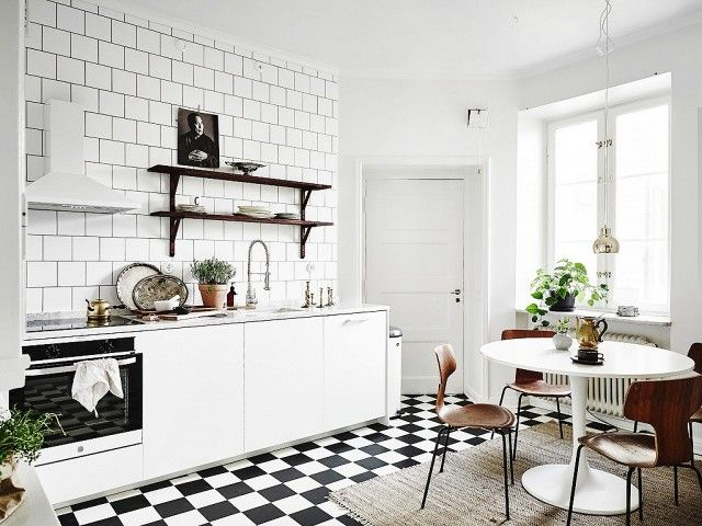 Swedish Kitchen With White Backsplash, Black And White Tiled Floors And A  Small Dining Nook