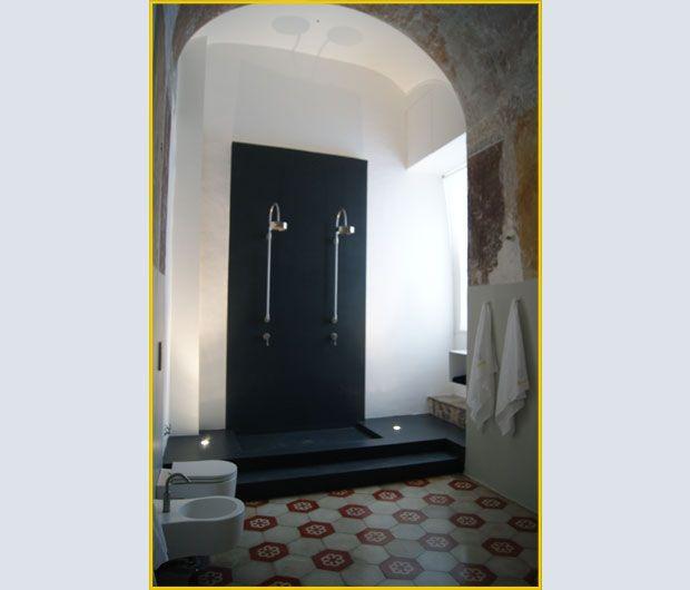 I pavimenti a piastrelle in cemento decorato dei primi del Novecento e le alte volte fanno risaltare la doppia doccia in resina grigio antracite della camera blu
