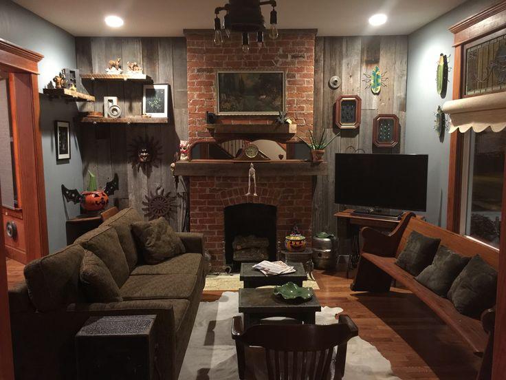 Vintage Farmhouse Industrial Living room heaven! Black Walnut mantel, barn wood, vintage decanters, church pew, train mold lighting,  and framed bugs.